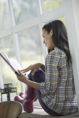 A young woman sitting reading a book.