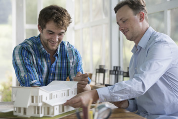 Two men looking at an architectural model of a house.