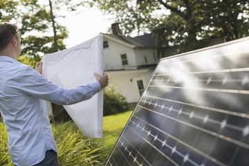 A man using a plan to place a solar panel in a farmhouse garden.