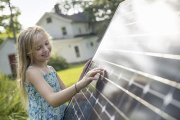 A young girl beside a large solar panel in a farmhouse garden.