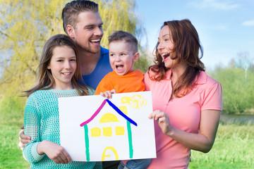 Familie hält das Traumhaus in den Händen