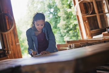 A woman working with reclaimed timber in a woodwork workshop.