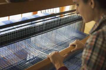 A woman seated at a wooden handloom creating a handwoven woollen fabric, with a blue and white pattern.