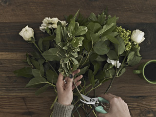 A woman holding secateurs and cutting the base of flower stems for a flower arrangement of white roses and green foliage.