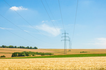 High voltage towers in agricultural fields.