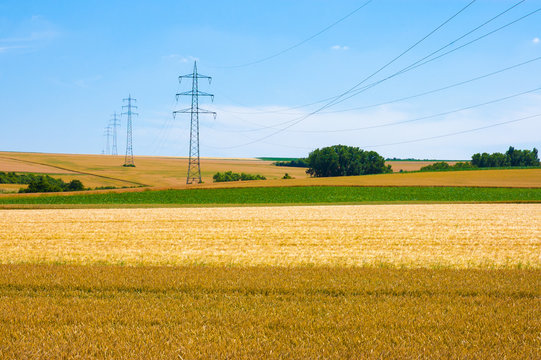 High-voltage towers in agricultural fields