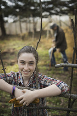 A young girl leaning on a fence, on an organic farm. A man digging the soil in the background.