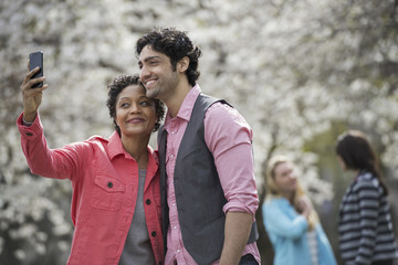 People outdoors in the city in spring time. White blossom on the trees. A young woman taking a photograph of herself and a young man.