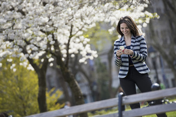 Outdoors in the city in spring time. New York City park. White blossom on the trees. A woman standing checking her mobile phone.