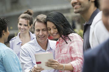 People outdoors in the city in spring time. New York City. A group of men and women, a couple in the centre looking at a digital tablet screen.