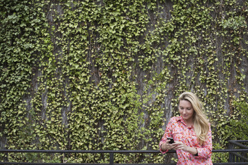 City life in spring. City park with a wall covered in climbing plants and ivy.  A young blonde haired woman checking her smart phone.