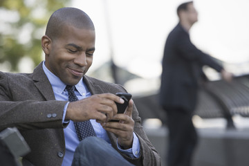Business people in the city. Keeping in touch on the move. A man seated using his smart phone. A man in the background.