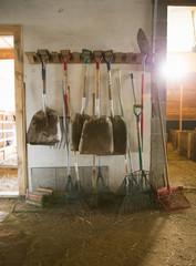 An organic farm. Livestock shed. Rack of shovels, hay rakes and a bootscraper.