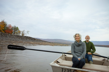 A couple, man and woman sitting in a rowing boat on the water on an autumn day.