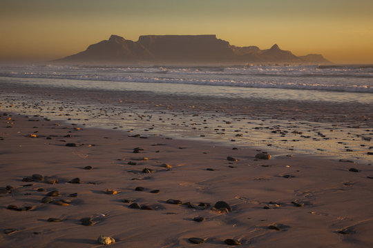 Table Mountain and the outline of Devil's Peak and Lion's Head, viewed from the shores of Blouberg beach in Western Cape.