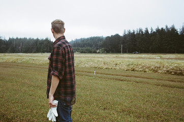 A cranberry farm in Massachusetts. Crops in the fields. A young man working on the land, harvesting the crop.