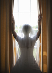 A woman in a wedding dress, wearing a light veil standing at a window with her arms up.