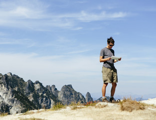 A hiker on the mountain summit, looking at a map. Surprise Mountain, Alpine Lakes Wilderness, in Mount Baker-Snoqualmie National Forest,