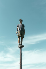 Man standing and balancing on metal post, looking towards expansive sky, Surprise Mt, Alpine Lakes Wilderness, Mt. Baker-Snoqualmie NF -