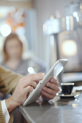 closeup on man's hands using a digital tablet in a bar