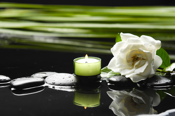 gardenia flower with green leaf ,candle on black stones