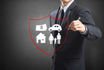 Business man drawing shield protecting family, insurance concept