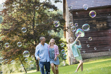 A family sitting on the grass outside a bar, blowing bubbles and laughing.