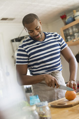 A man in a kitchen using a knife to slice an orange.