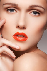 Close-up portrait of beautiful woman's purity face with bright red lips make-up