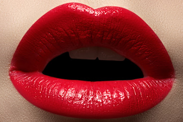 Close-up of woman's lips with bright fashion red makeup. Macro bloody lipstick make-up