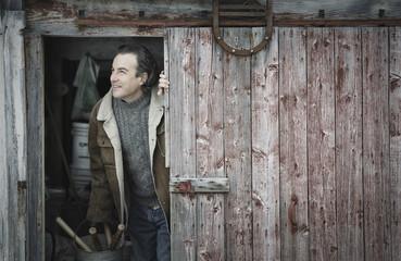 Man at open barn door
