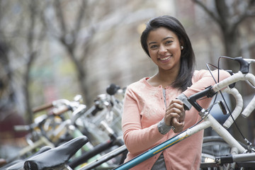 City life in spring. Young people outdoors in a city park. A young woman with black hair, wearing a peach coloured shirt, standing beside a rack of parked locked bicycles.
