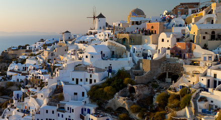 The windmills of Santorini in Greece. A hilltop town of whitewashed houses. Sunset.