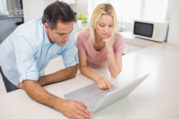 Concentrated couple using laptop in kitchen
