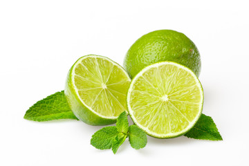 Three green limes and peppermint leaves on white background
