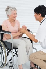 Doctor talking to a senior patient in wheelchair