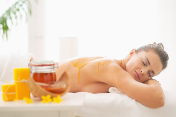 Relaxed young woman receiving honey spa therapy