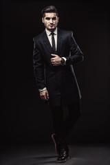 Full-length portrait of handsome stylish man in elegant black su