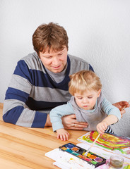 Father and little boy of two years having fun painting