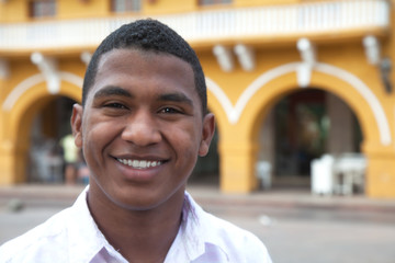 Young guy in a colonial town laughing at camera