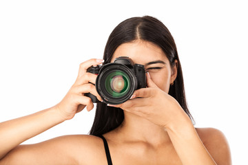 Closeup portrait of a young woman holding a camera over white