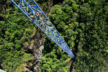 Workers climing supporting pole, Sky Bridge, Langkawi island