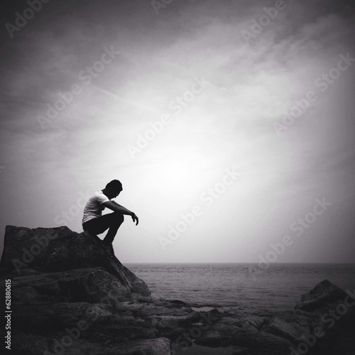 man sitting alone on the beach stock photo and royalty free images