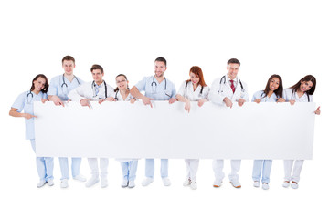 Friendly physicians holding a blank banner