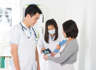 asian pregnancy check up with doctor and mother with ultrascan p