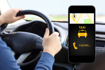 phone with interface taxi on a screen on a background man drivin