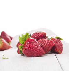 Large strawberries on white wooden table , isolated