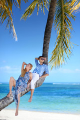 Beautiful young couple sitting on palm tree