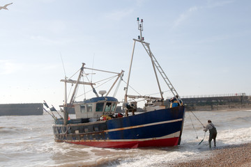 Fishing boat being landed on beach