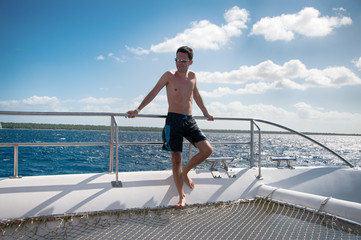 Man holing a rail on a catamaran in the Caribbean Sea